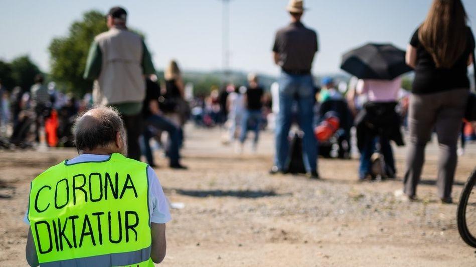 """Im Bildvordergrund sitzt ein uns abgewandter Mann auf einer Picknickdecke und trägt eine neongelbe Warnweste. Auf deren Rückseite steht in Großbuchstaben geschrieben: """"Corona-Diktatur stoppen"""". Im Hintergrund sind Teilnehmer eine Kundgebung zu erkennen."""