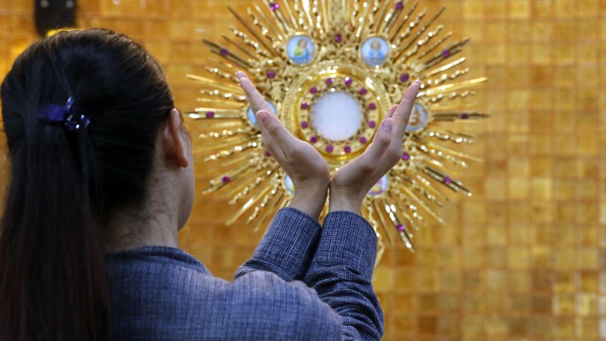 Eine Frau betet vor einer Monstranz mit einer geweihten Hostie, die Christus symbolisiert.