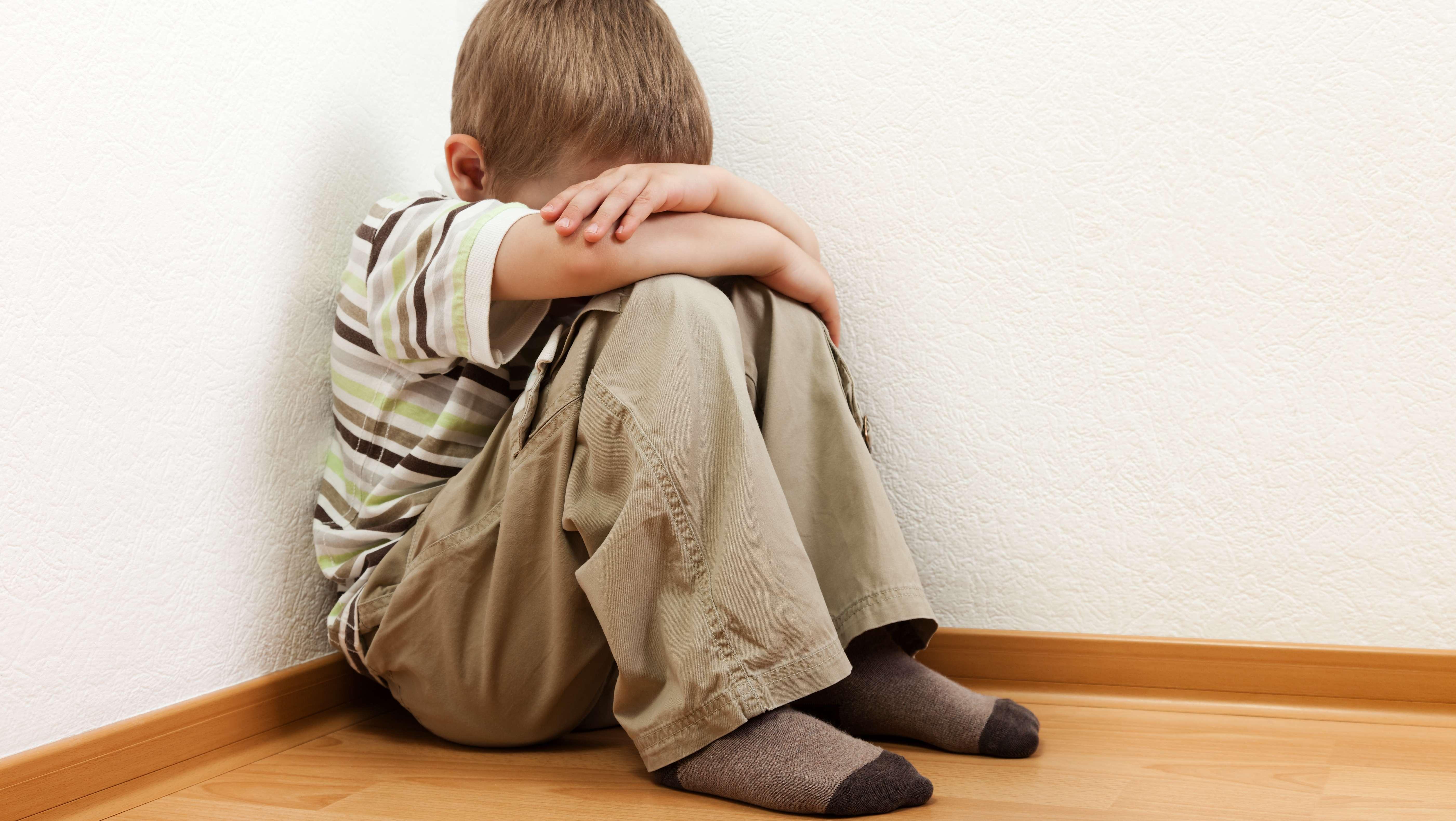 Ein Kind hat seinen Kopf hinter seinen Armen versteckt