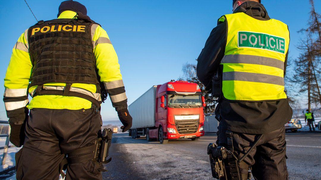 Tschechische Polizisten stehen an einem Kontrollpunkt, im Hintergrund fährt ein Lastwagen.