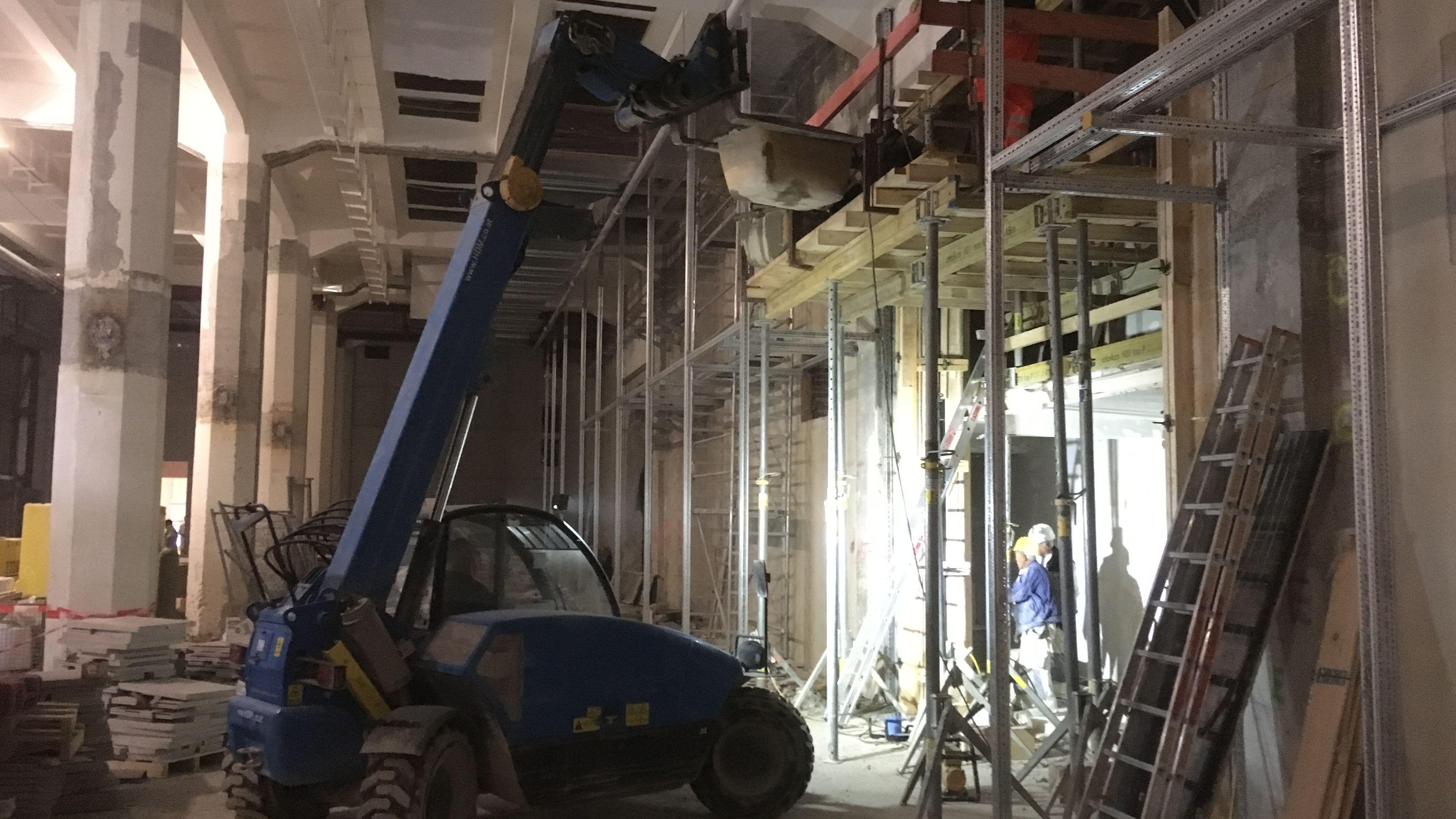 Wände werden eingerissen und neu eingezogen. Hier liefert ein Hebekran eine Wanne mit flüssigem Beton an, der von den Arbeitern auf dem Gerüst von Hand in eine senkrechte Verschalung gekippt wird.