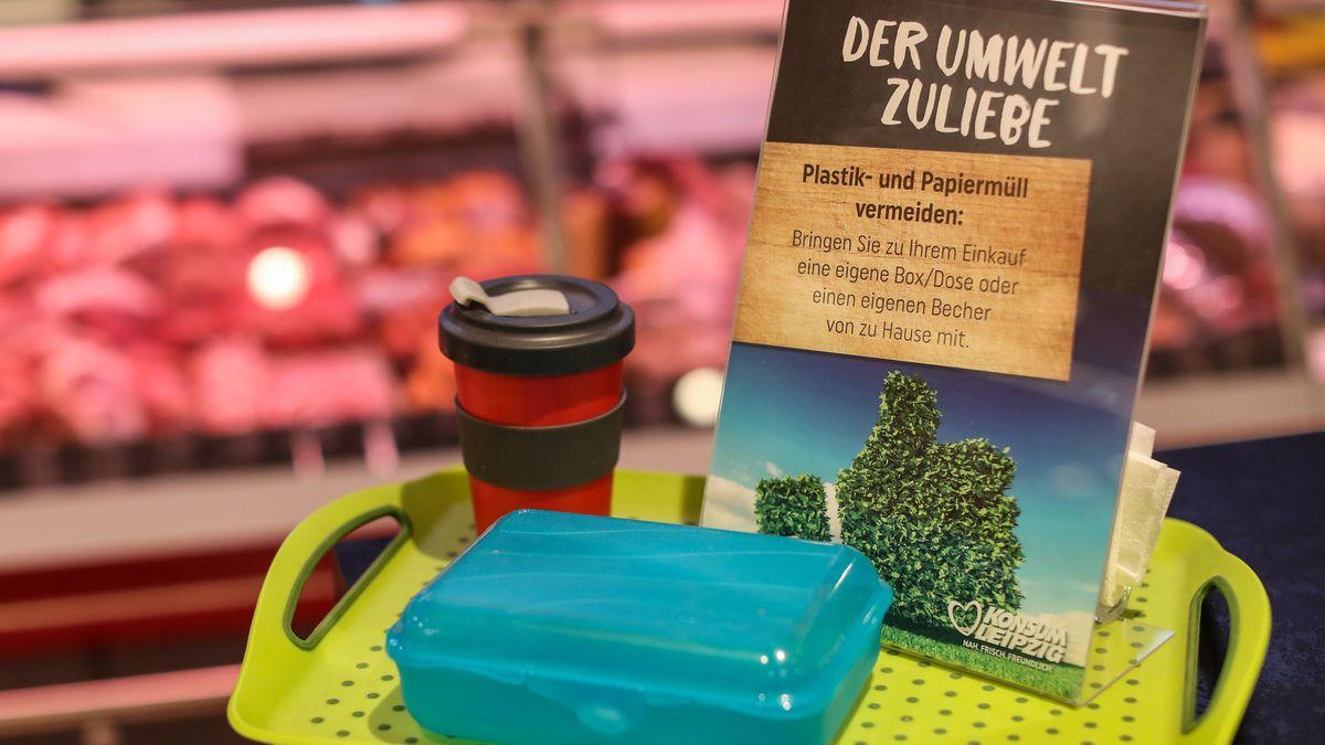 """Ein Schild """"Der Umwelt zuliebe"""" steht neben einer Plastikbox und einem Mehrweg-Kaffeebecher auf einem Tablett"""