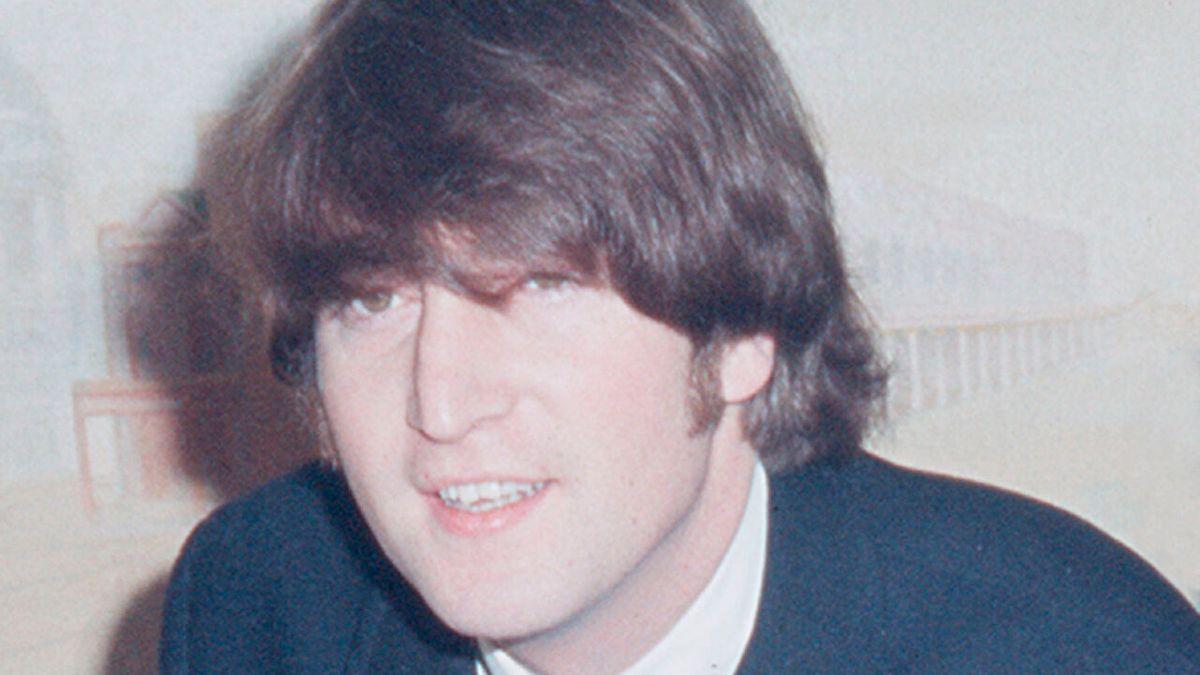 Lohn Lennon ohne Brille auf einer Pressekonferenz der Beatles 1965.