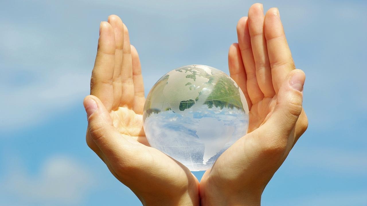 Symbolbild: Wir müssen unsere Erde vor Zerstörung bewahren. Hände umfassen schützend eine erdähnliche Glaskugel.
