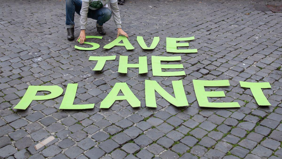 """Eine """"Fridays for Future""""-Aktivistin legt den Schriftzug """"Save the planet"""" auf dem Boden aus"""