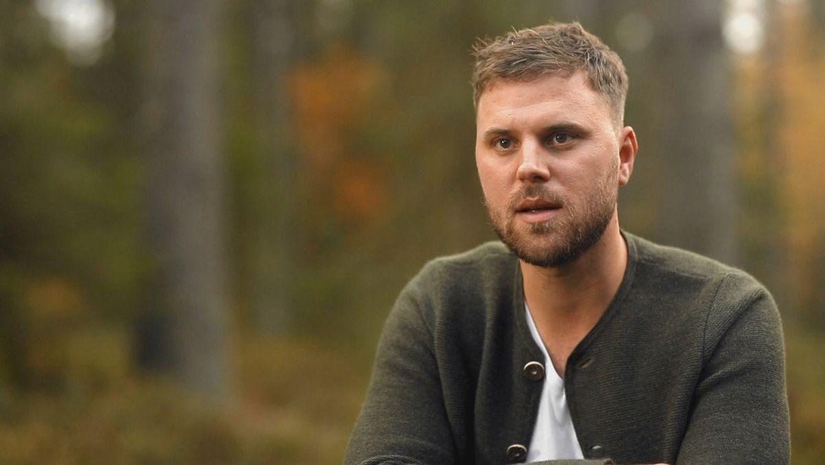 Man sieht einen jungen Mann mit kurzen Haaren und Bart, der burschikos im Wald sitzt.
