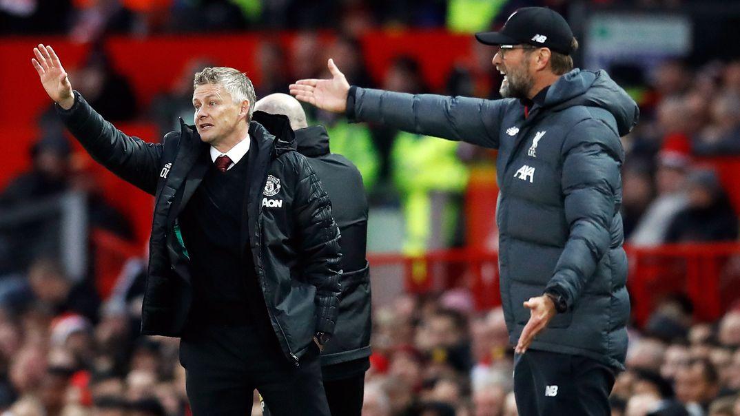 Ole Gunnar Solskjaer (l), Trainer von Manchester United, und Jürgen Klopp, Trainer vom FC Liverpool, gestikulieren nebeneinander vom Spielfeldrand aus (Archiv)