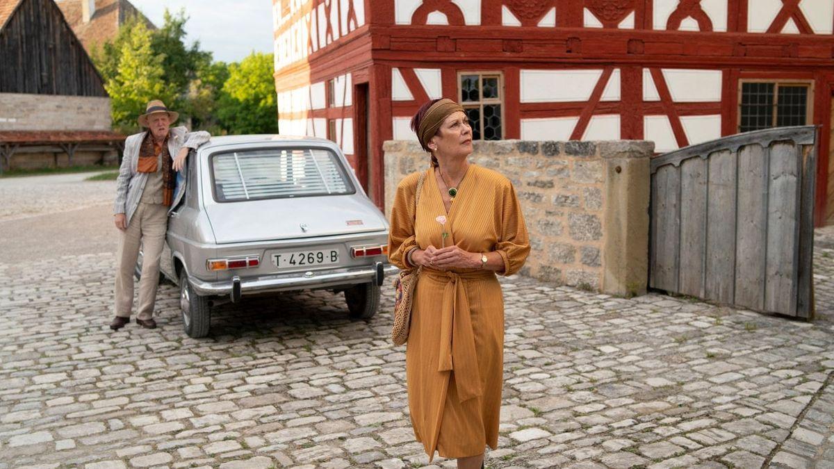 Ein Mann im Anzug mit einem grauen französischen Kleinwagen und eine elegante Frau vor einem Fachwerkhaus