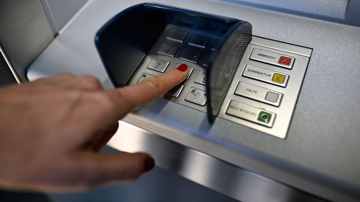 Weibliche Hand gibt PIN am Geldautomat ein.