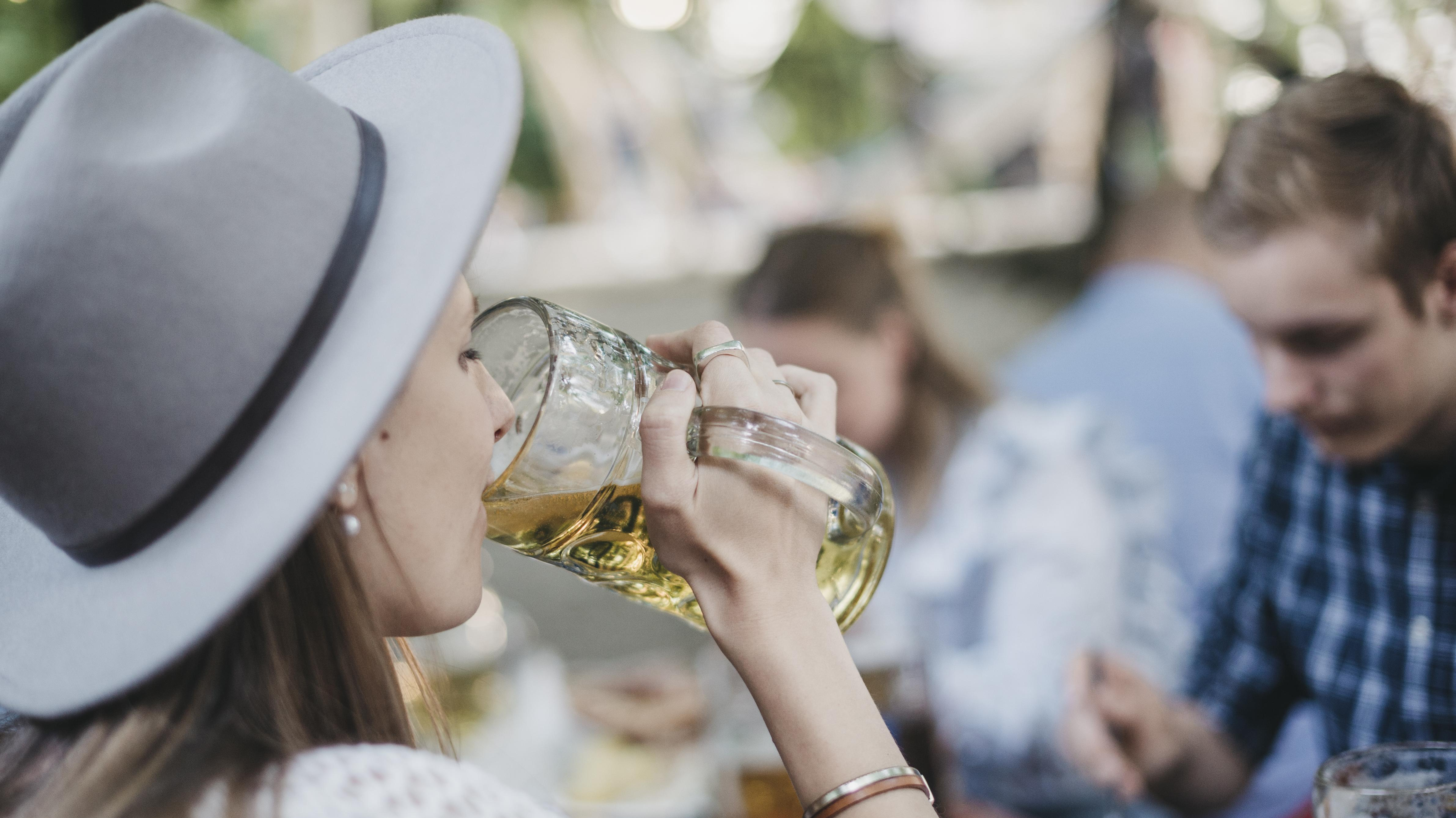 Eine Frau trinkt in einem Biergarten eine Mass Bier.