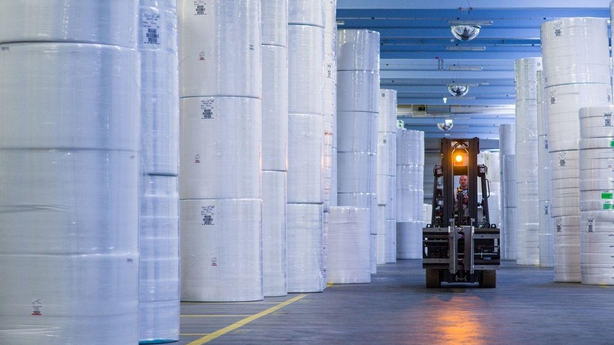 Ein Gabelstapler fährt durch eine Halle in der große Rollen Vliesstoffe gelagert werden.