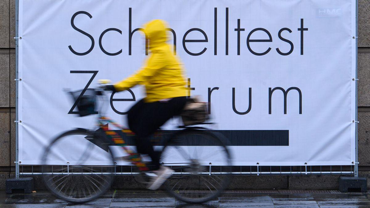 Eine Fahrradfahrerin vor einem Testzentrum.