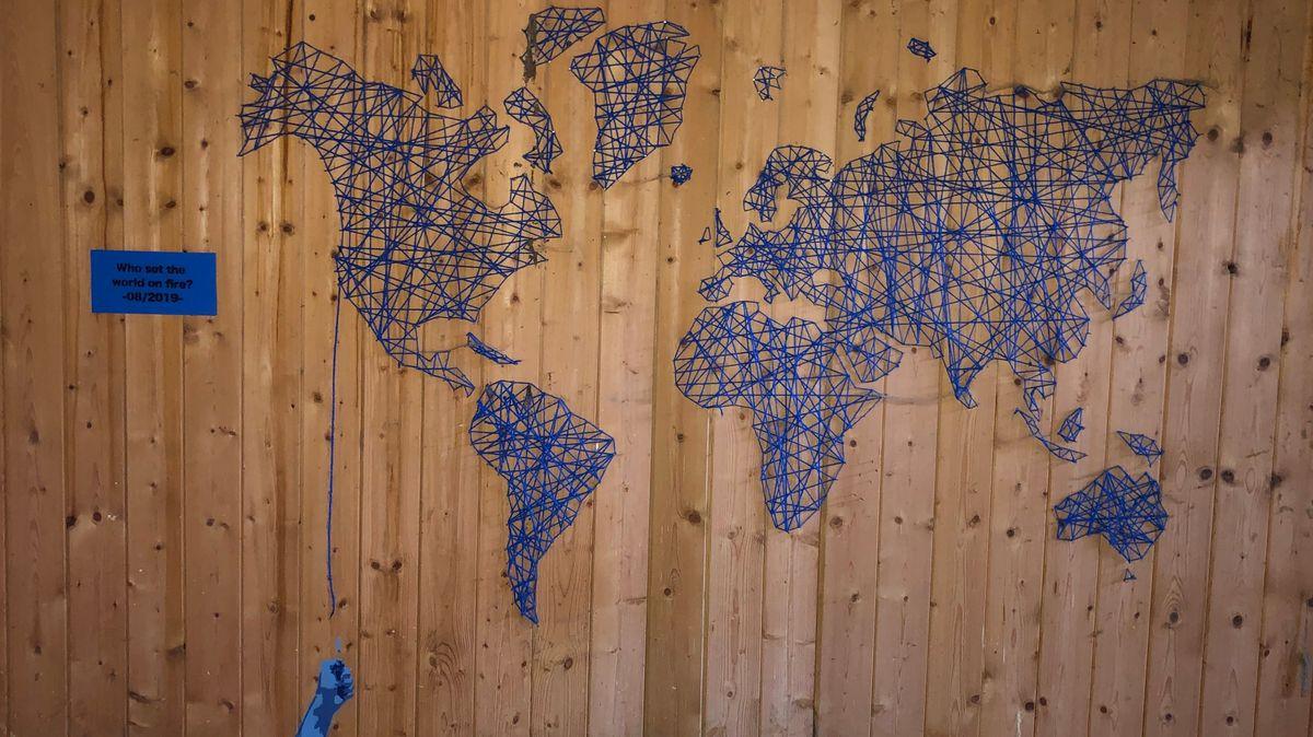 Blaues Kunstwerk: Weltkarte aus Fäden und Nägeln.