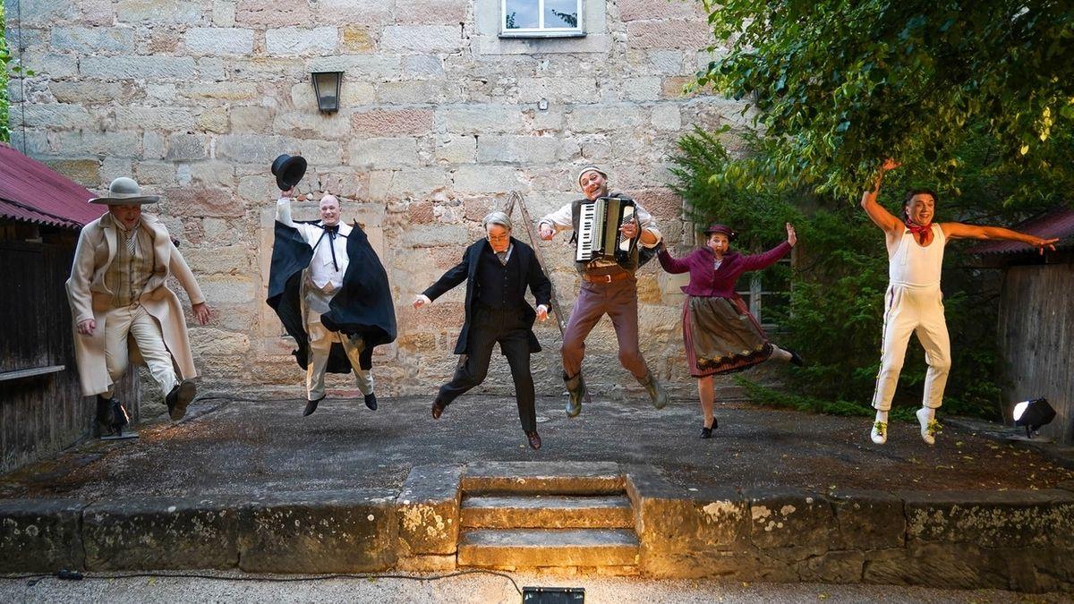 Sechs Schauspieler springen auf einer Bühne aus Stein in die Luft.