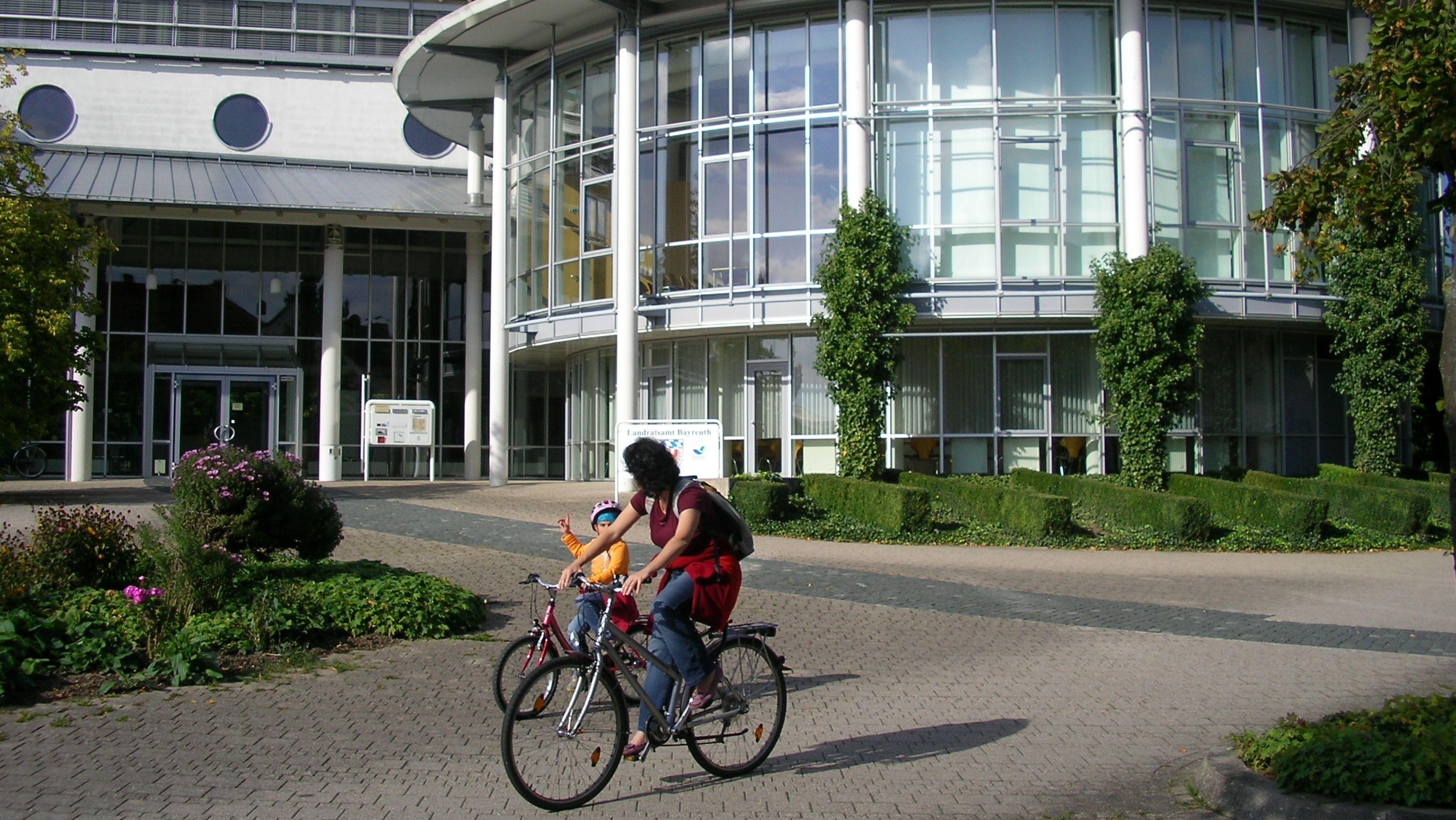 Eine Frau und ein Kind fahren mit Fahrräder am Landratsamt in Bayreuth vorbei.