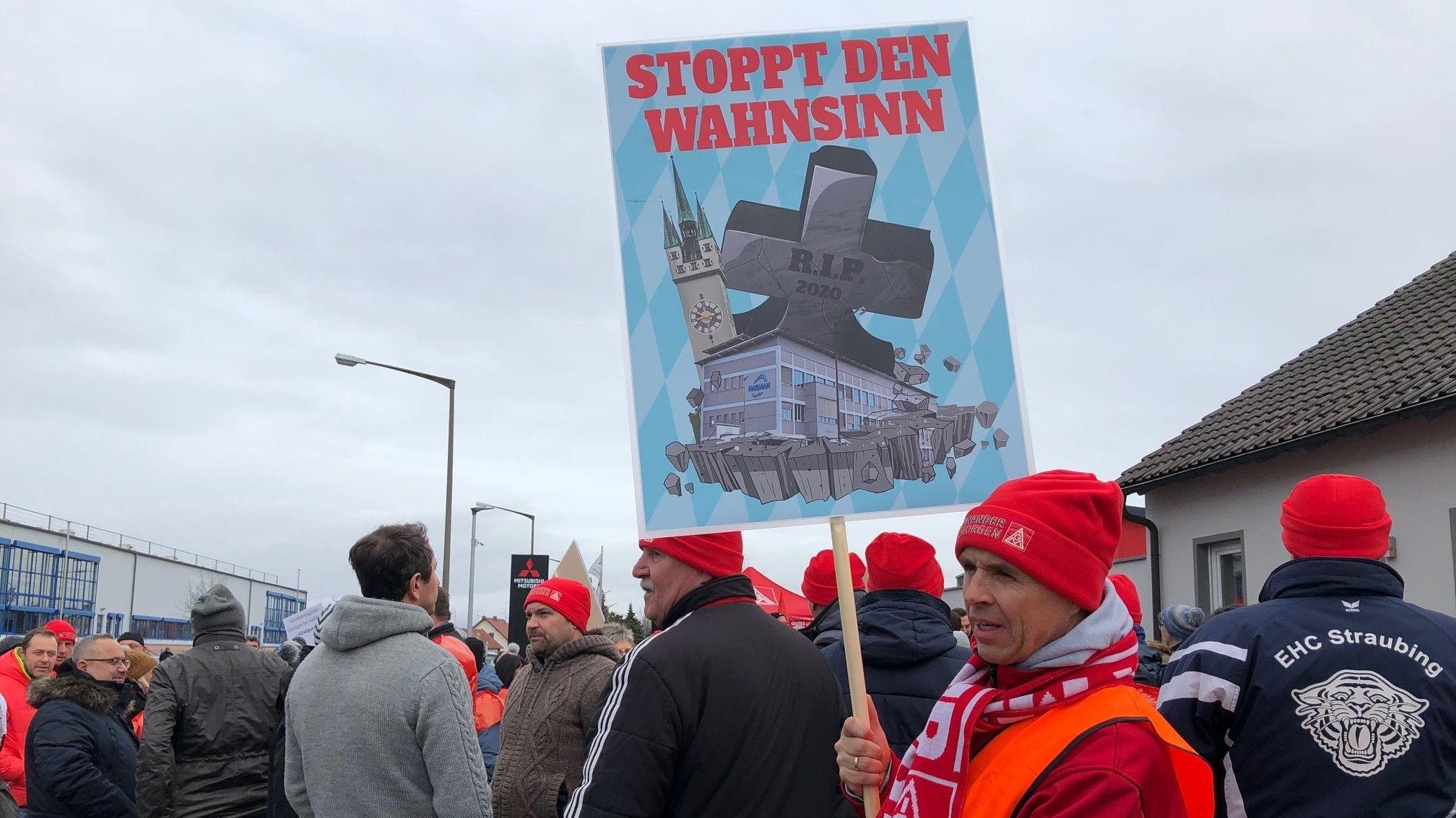 """Ein Harman-Mitarbeiter hält ein Schild hoch: """"Stoppt den Wahnsinn"""""""