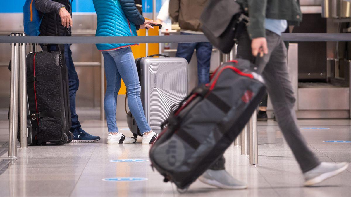 Reisende mit Koffern an einem Check-In-Schalter am Flughafen München