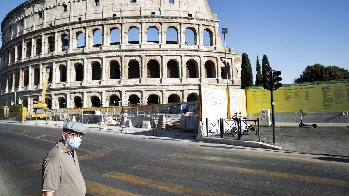 Ein Mann mit Mund-Nasen-Schutz steht vor dem Colloseum in Rom.