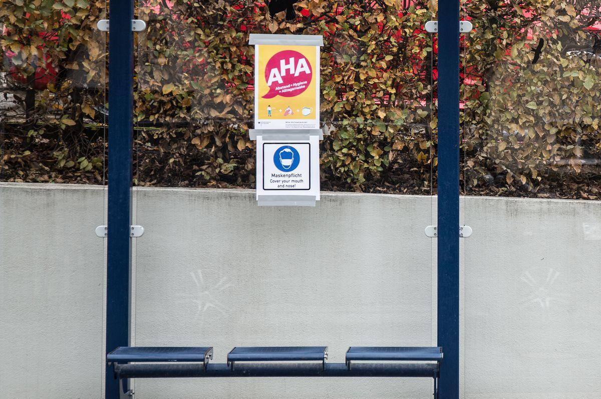 Aufruf zum Einhalten der AHA-Regeln an einer Bushaltestelle