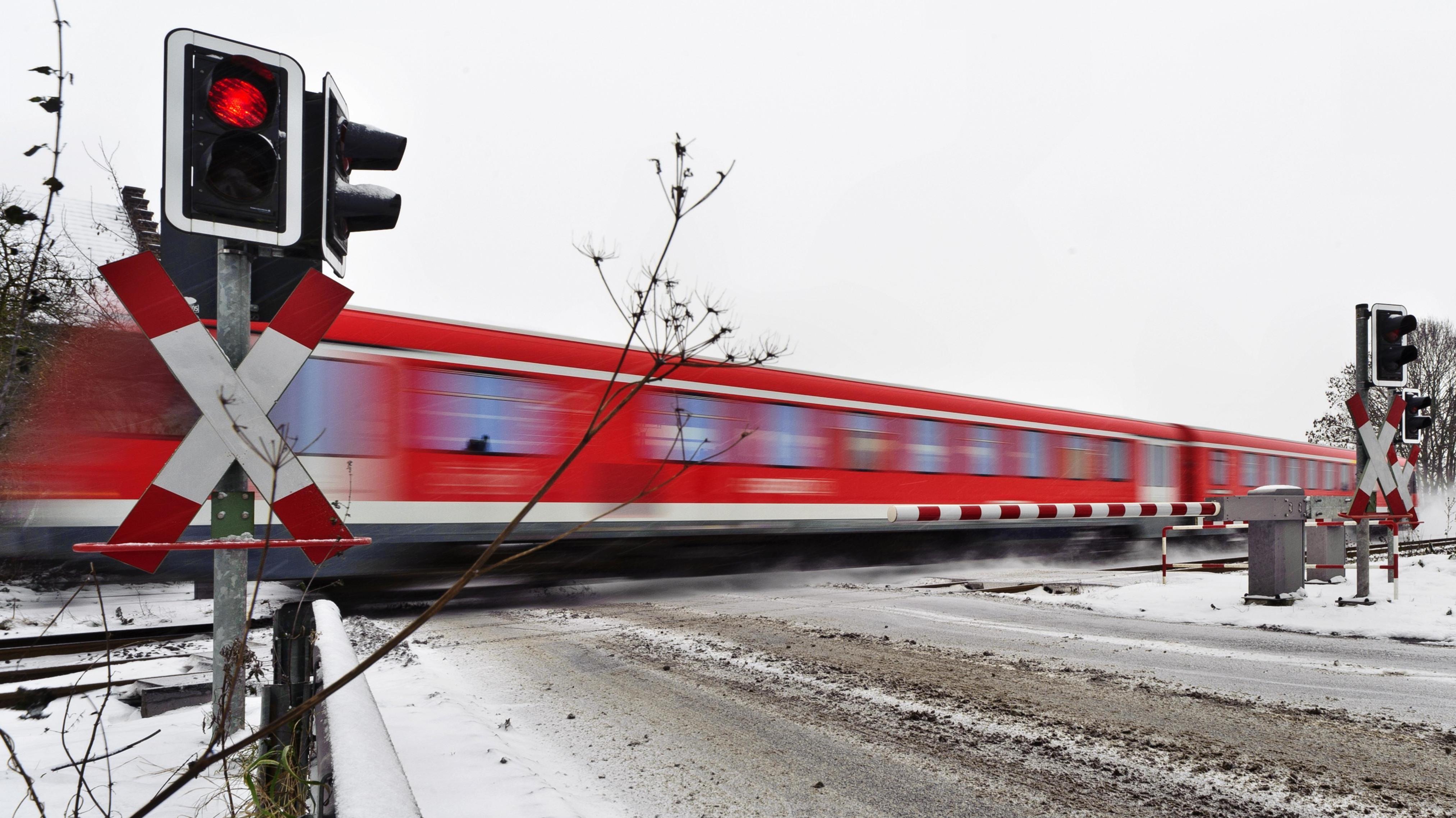 Personenzug passiert einen Bahnübergang im Winter