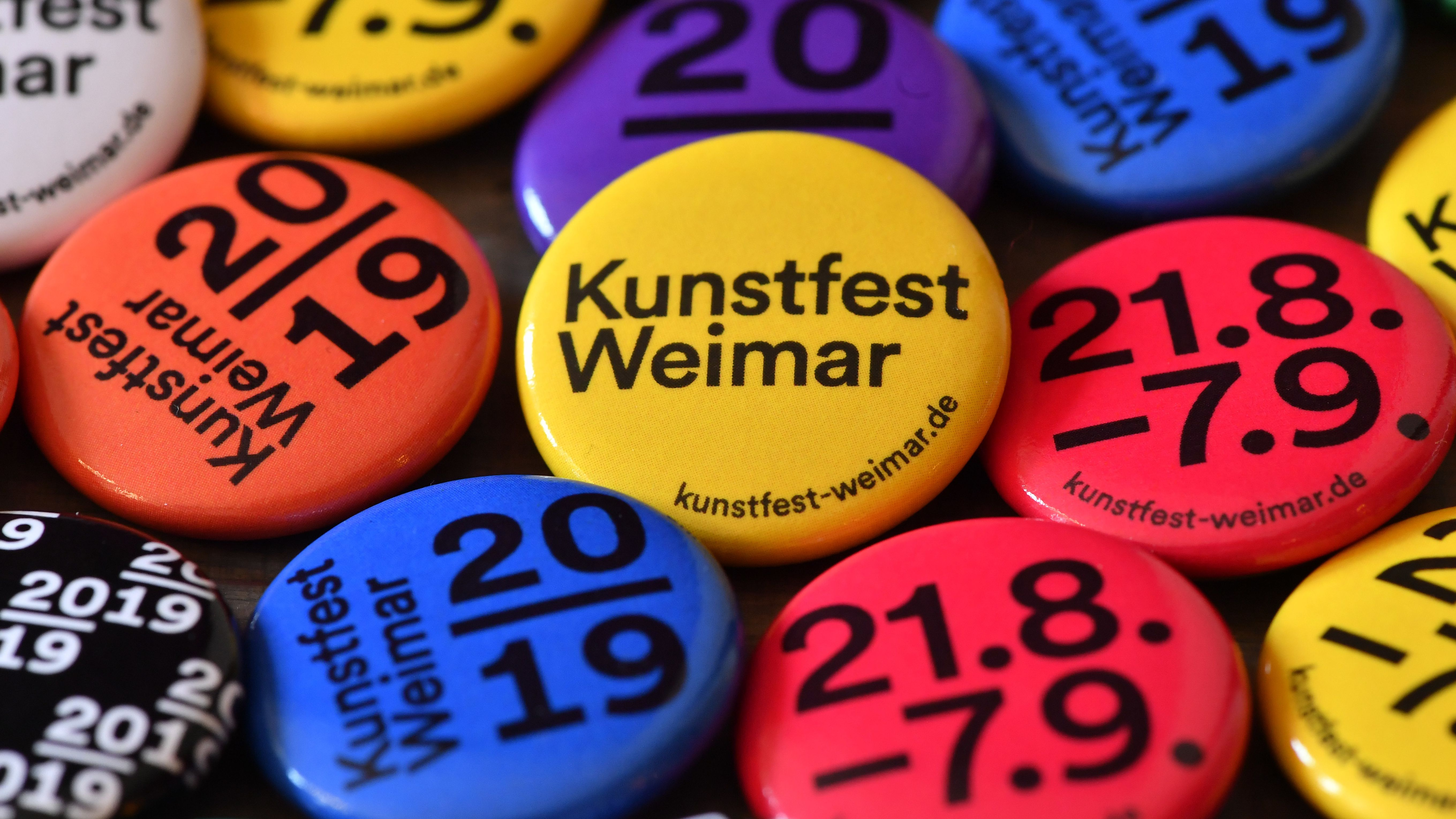 Eine Ansammlung gelber, pinker und blauer Anstecker für das Kunstfest Weimar 2019