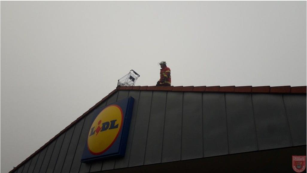 Die Feuerwehr holt den Einkaufswagen vom Supermarktdach