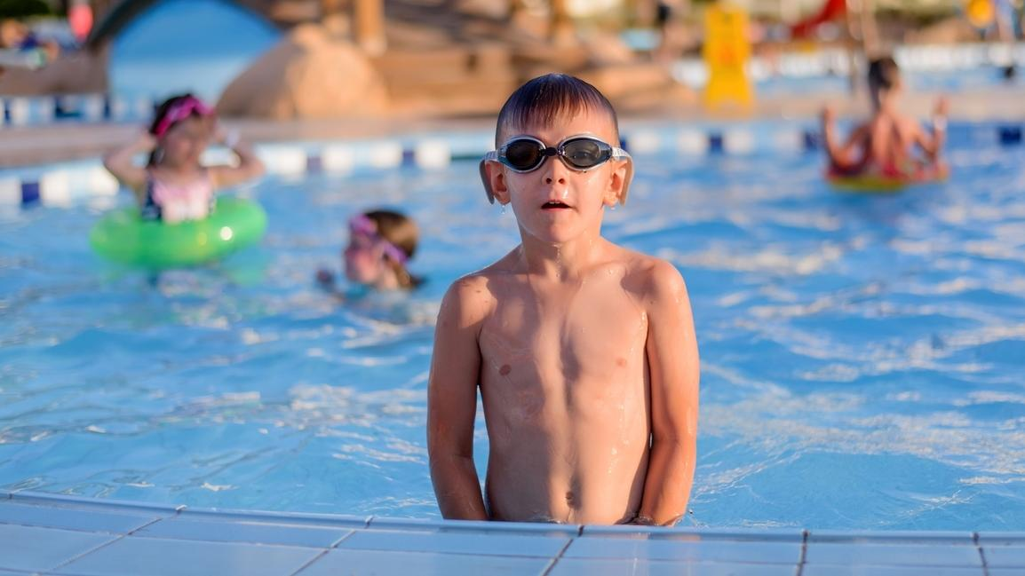 Ein Junge planscht im Freibad. Der Chlor-Geruch im Schwimmbad entsteht erst in Kombination mit Urin.