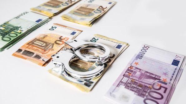 Symbolbild - Betrug: Handschellen auf Geldscheinen.