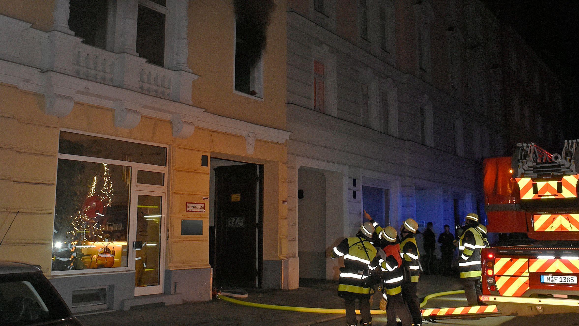 Feuerwehrleute stehen neben einem einem Löschfahrzeug und schauen auf das Fenster im ersten Stock, aus dem schwarzer Rauch dringt.