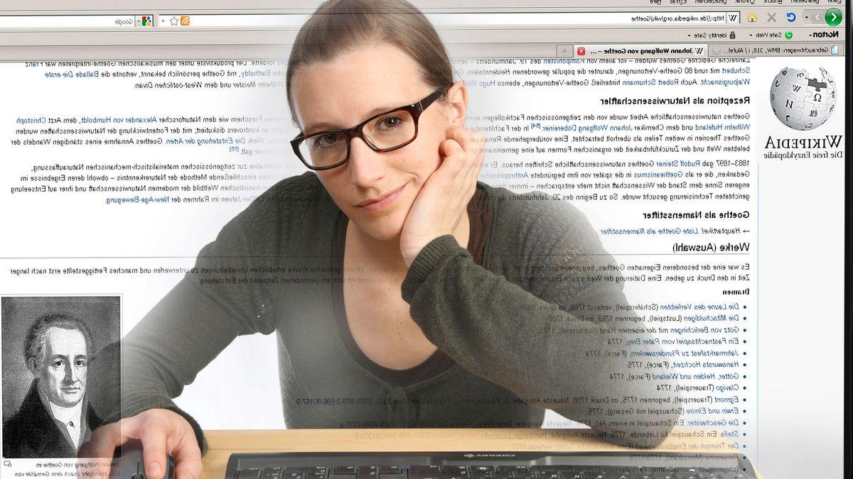 Junge Frau sitzt am Computer, surft im Internet, recherchiert auf der Seite des Onlinelexikons Wikipedia.