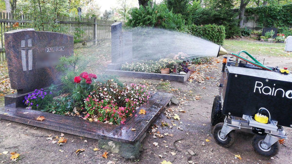 Ein Gießroboter bewässert ein Grab