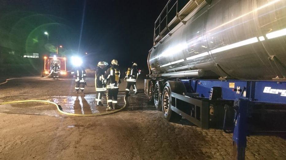 Feuerwehrmänner stehen in Hammelburg neben einem Sattelauflieger, an dem zuvor die Reifen gebrannt hatten.