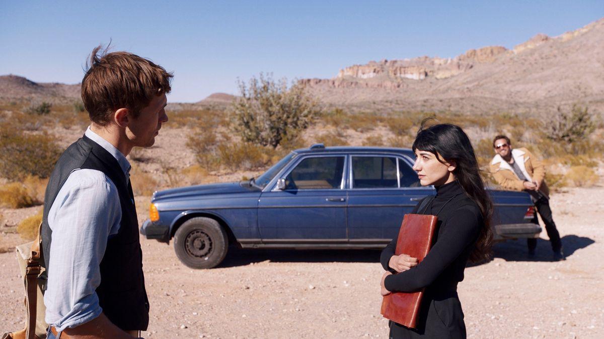 """Zwei Männer und eine Frau stehen bei einem Auto in einer verlassenen US-Wüstenlandschaft (Szennfoto aus dem Film """"Land of Dreams"""""""