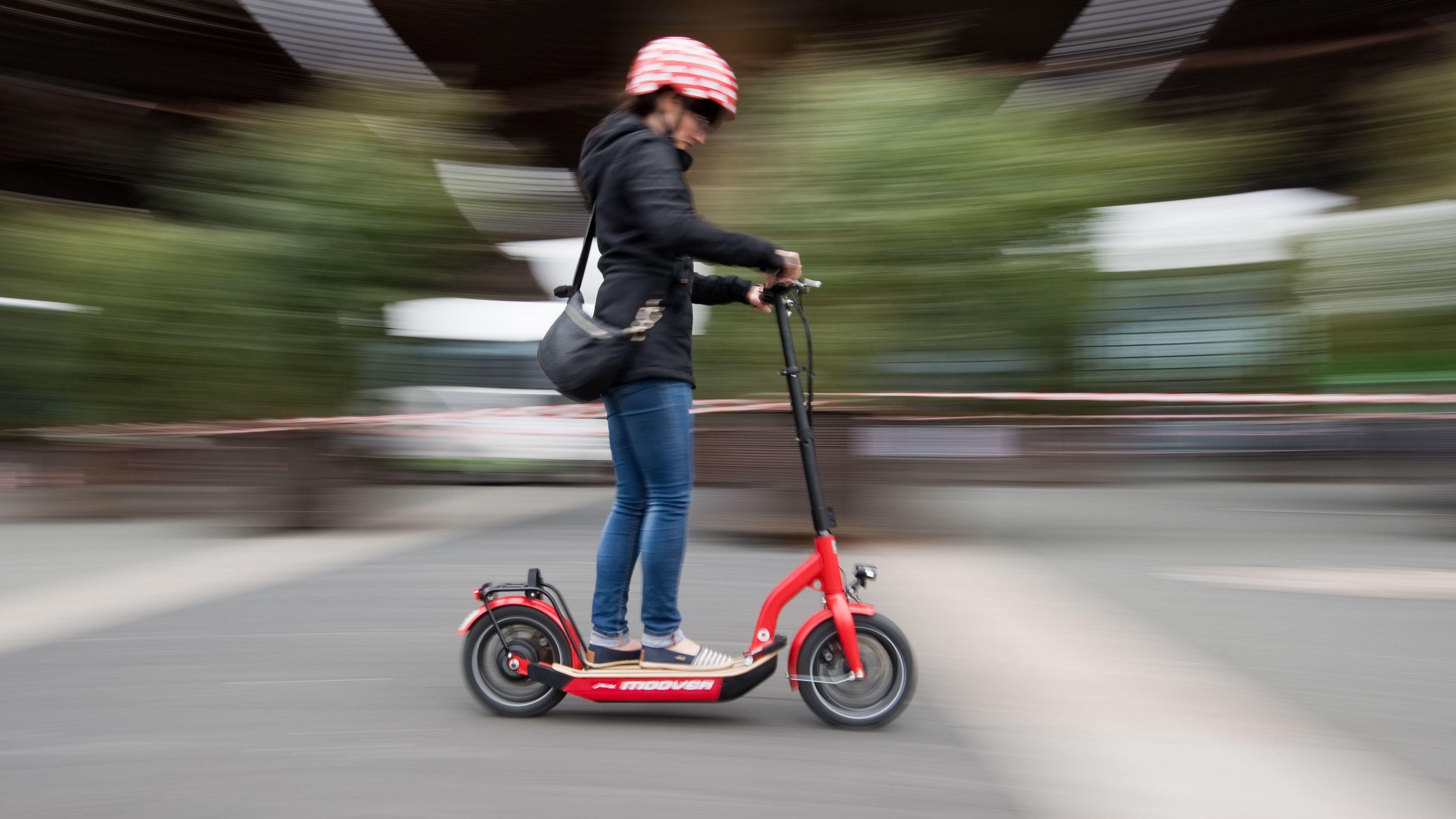 Eine Frau ist auf einem E-Scooter unterwegs