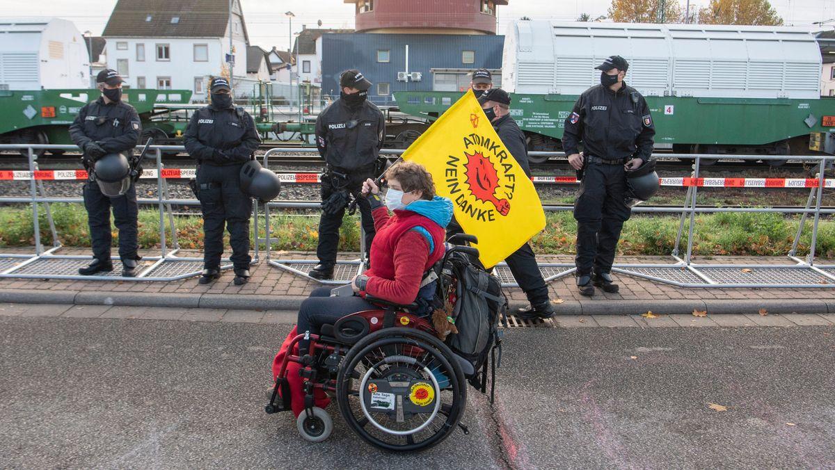 """Rolli-Fahrer mit """"Atomkraft, nein danke""""-Flagge vor sechs Polizisten"""