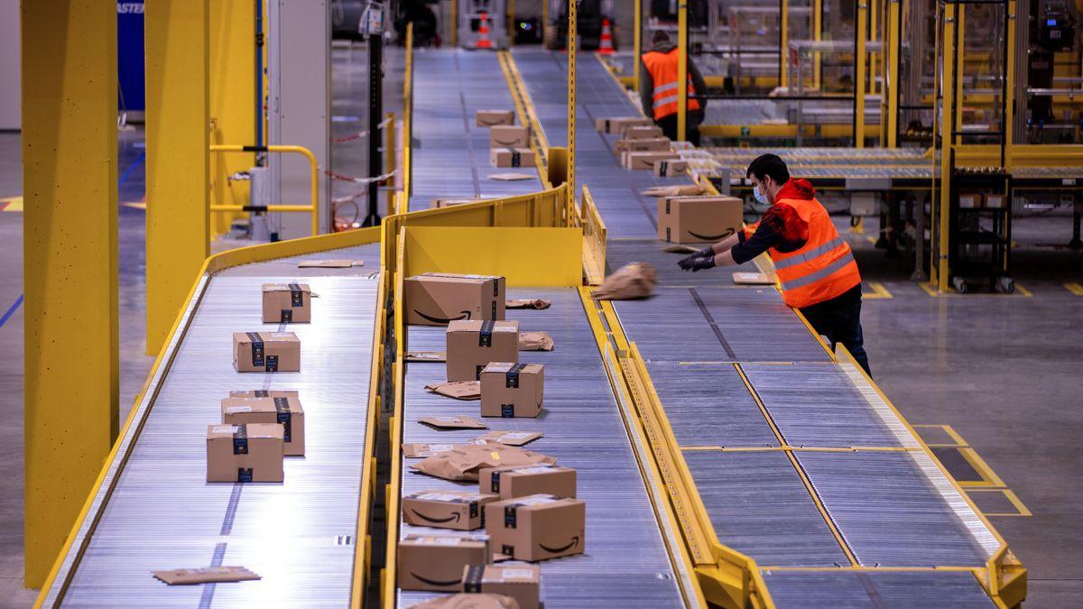 Ein Mitarbeiter sortiert an einem Transportband Paketsendungen (Symbolbild).