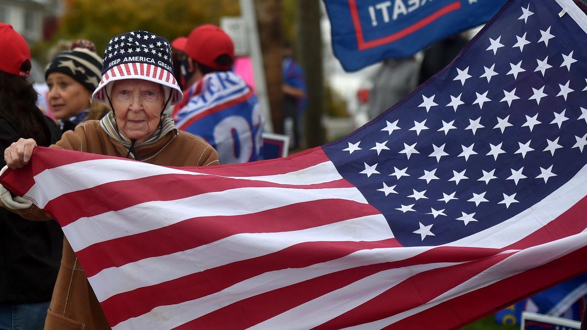 """USA, Dallas: Eine Anhängerin des US-Präsidenten Trump trägt einen Keep-America-Great""""-Hut und hält eine amerikanische Flagge."""