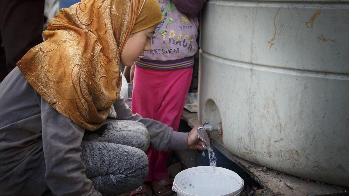 Syrerin zapft Trinkwasser ab