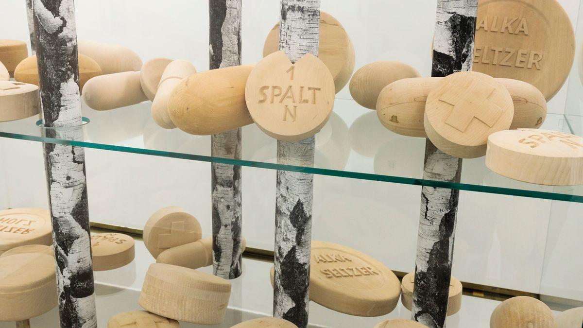 """Martin Kippenbergers Arbeit:  """"Jetzt geh ich in den Birkenwald, denn meine Pillen wirken bald"""" aus Birkenstämmen, und hölzernen Pillen"""