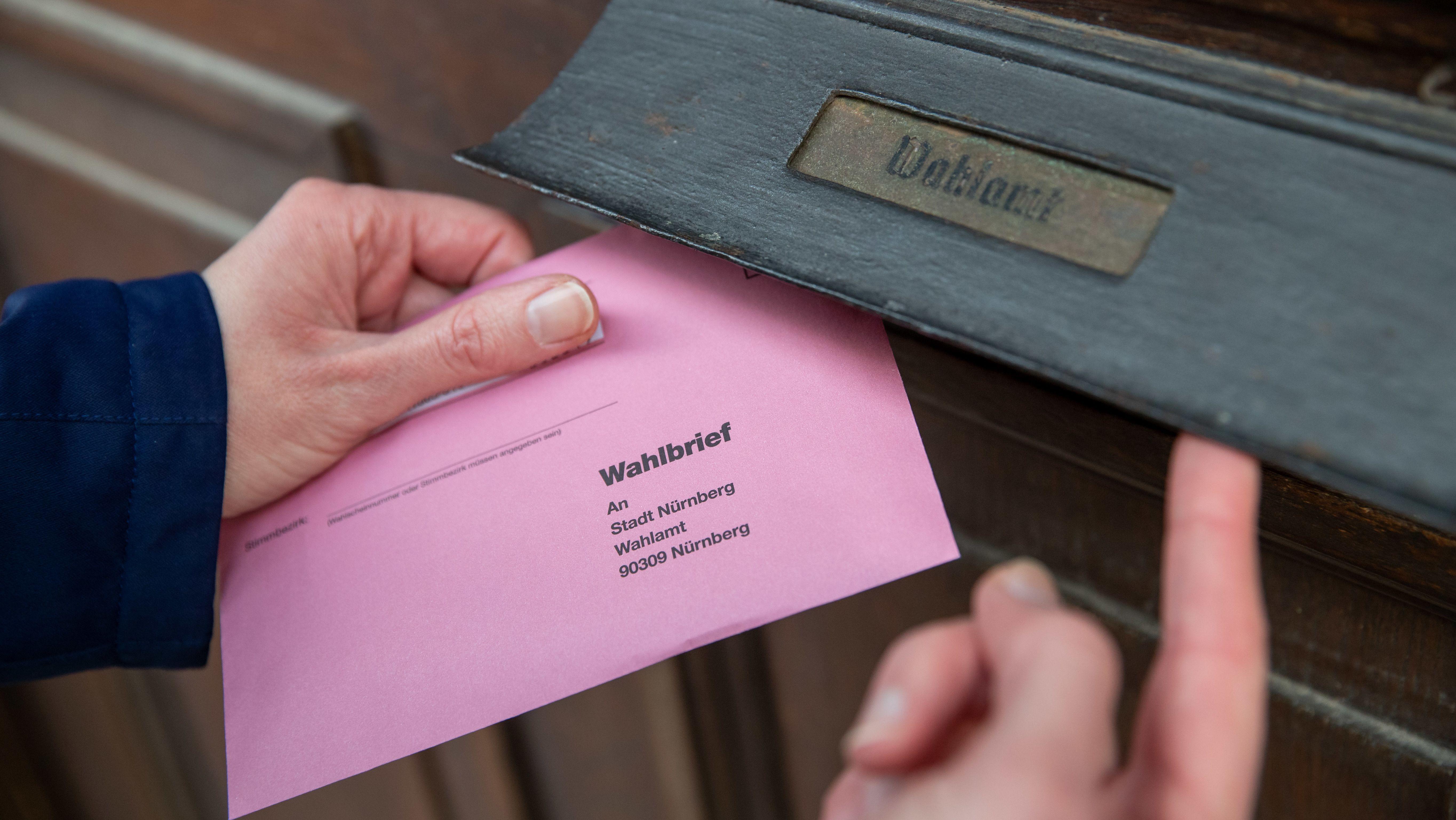 Eine Frau wirft ihre Briefwahlunterlagen für die Oberbürgermeister-Stichwahl am 29. März in Nürnberg in den Briefkasten des Wahlamtes.