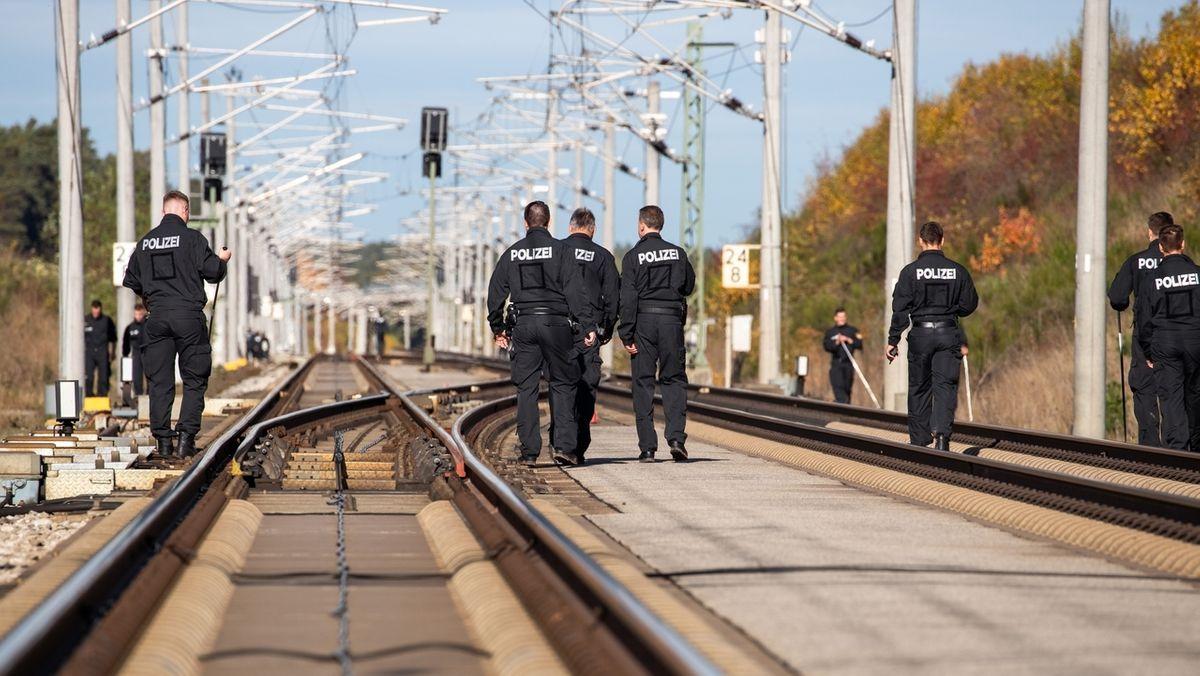 Polizisten durchsuchen nach dem versuchten ICE-Anschlag in Allersberg die Bahnstrecke.