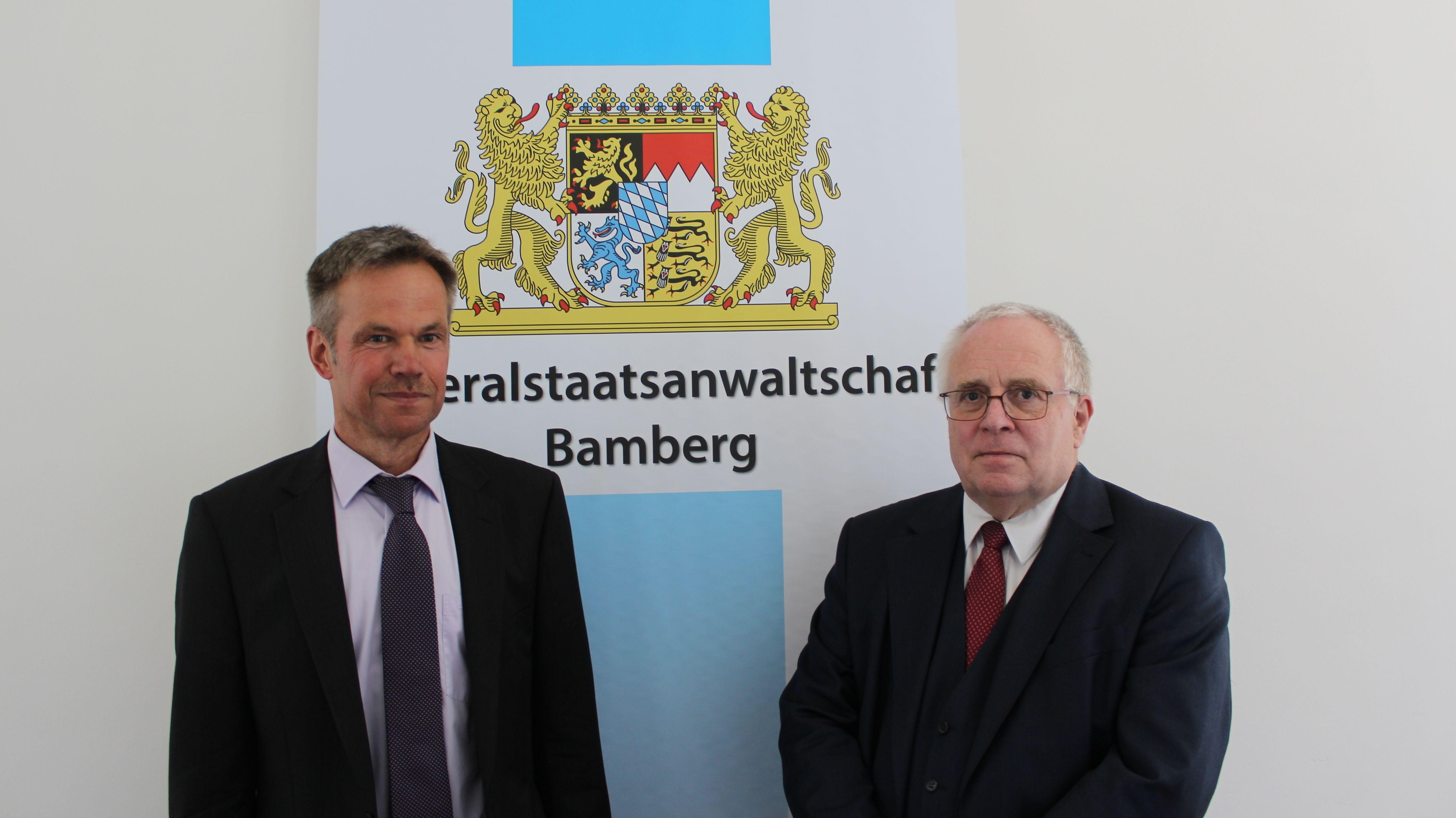 """Martin Dippold und Thomas Janovsky  stehen vor einem Aufsteller mit der Aufschrift """" Staatsanwaltschaft Bamberg"""""""