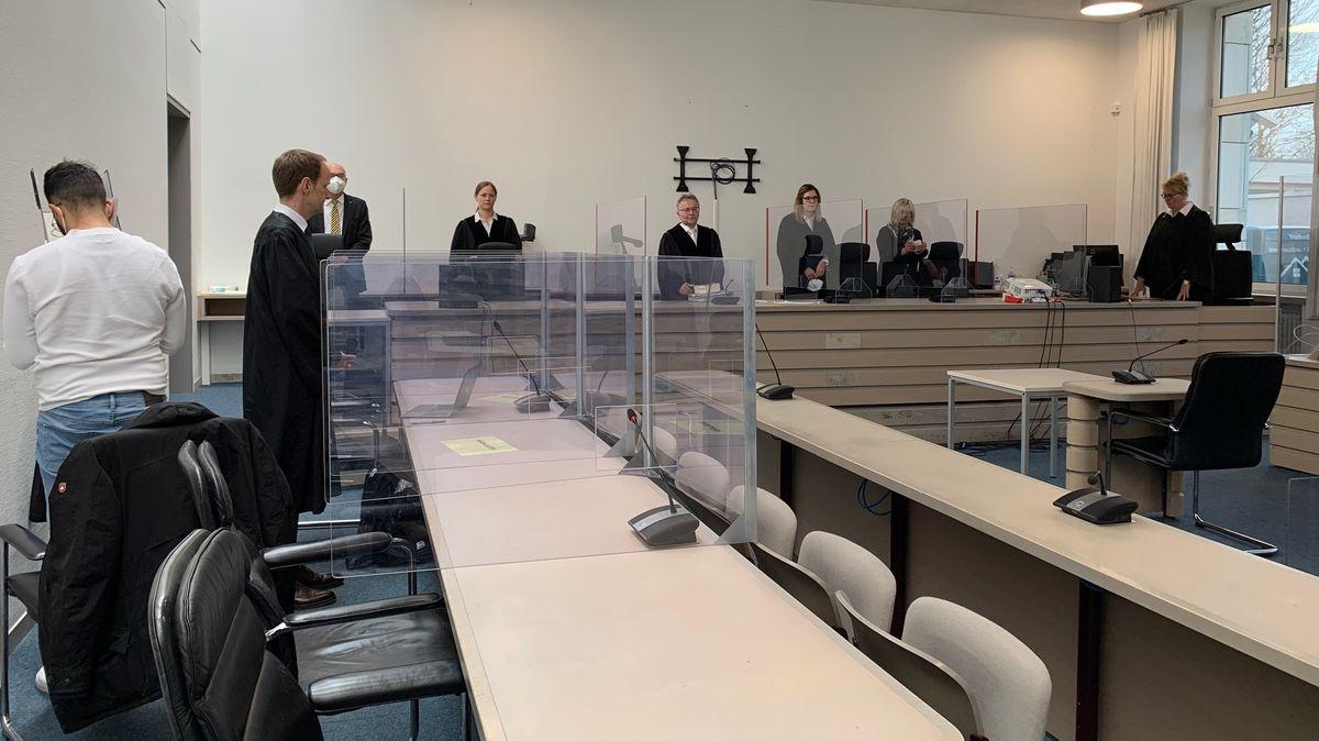 Der Angeklagte wendet sich im Gerichtssaal von den Fotografen ab.