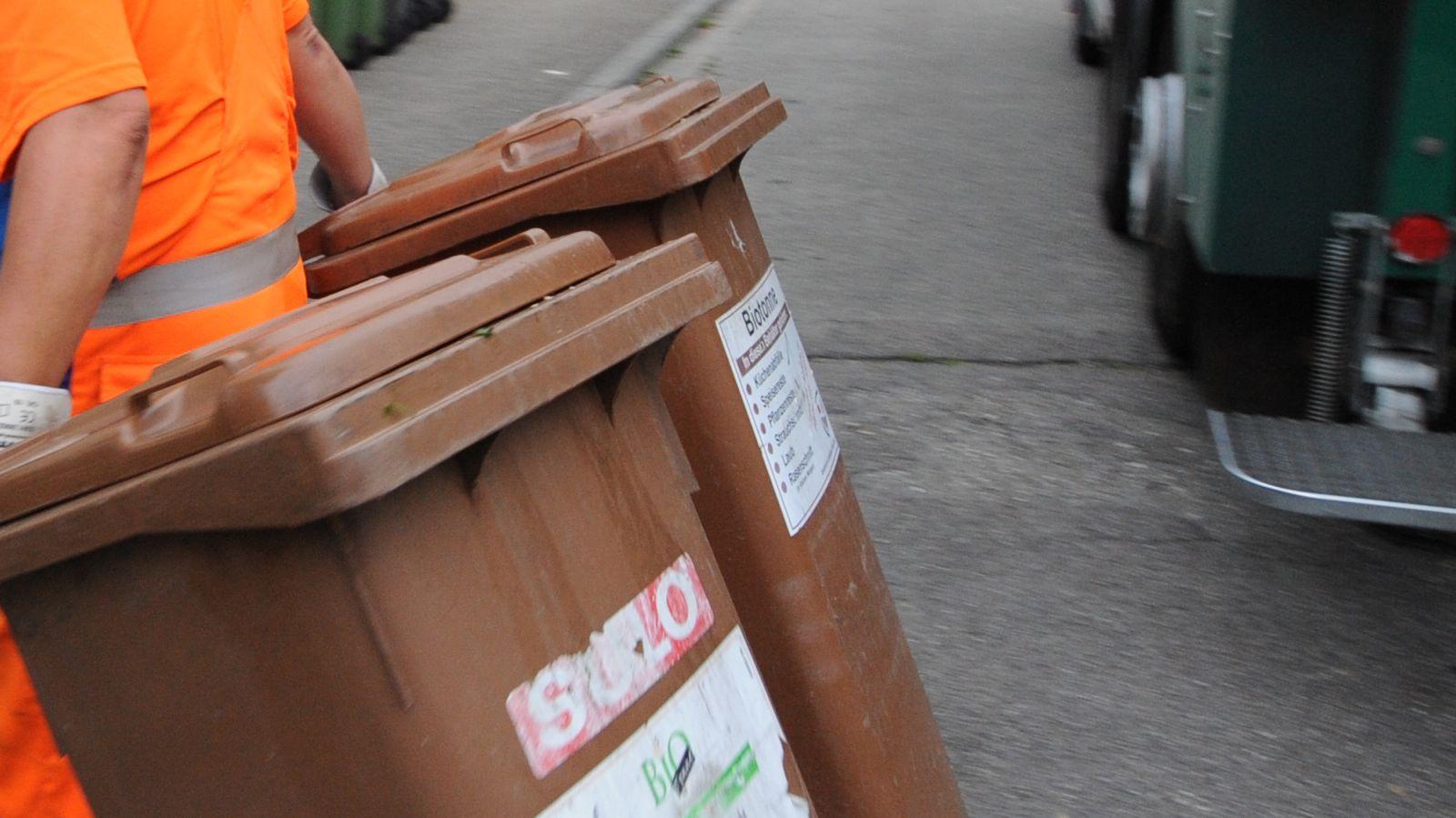 Ein Beschäftigter der Müllabfuhr zieht zwei Biotonnen hinter sich her (Symbolbild)
