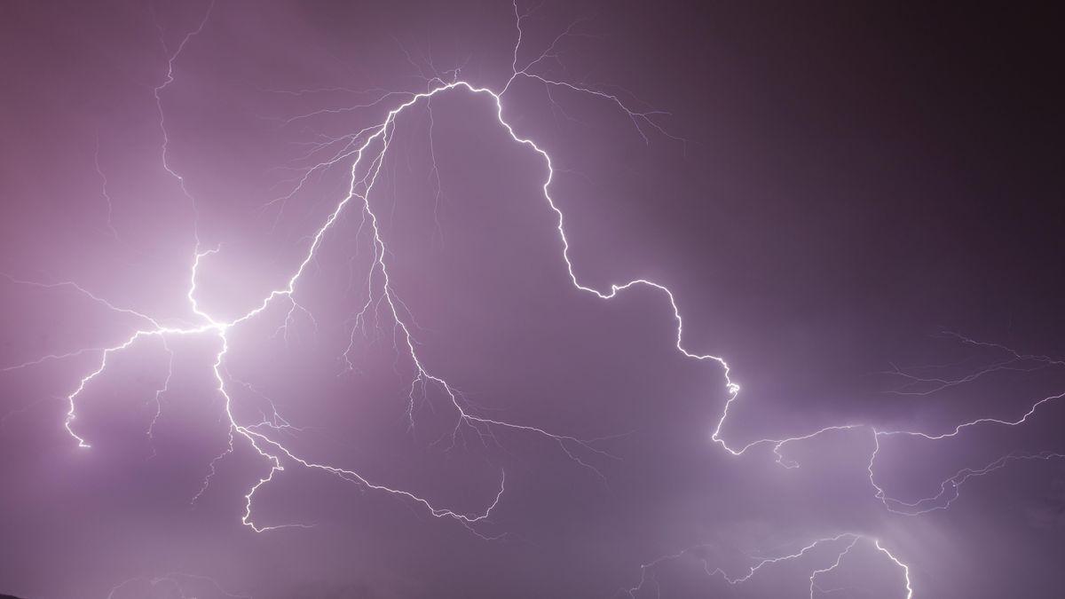 Mehrere Blitze entladen sich am lila-blauen Himmel