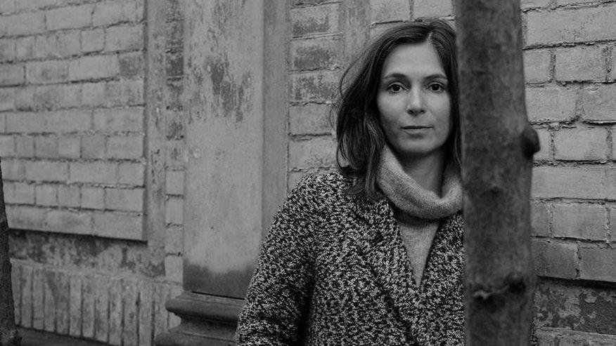 Schwarz-Weiß-Bild: Lydia Daher in einem Wintermantel, schaut in die Kamera, im Vordergrund ein schmaler Baumstamm