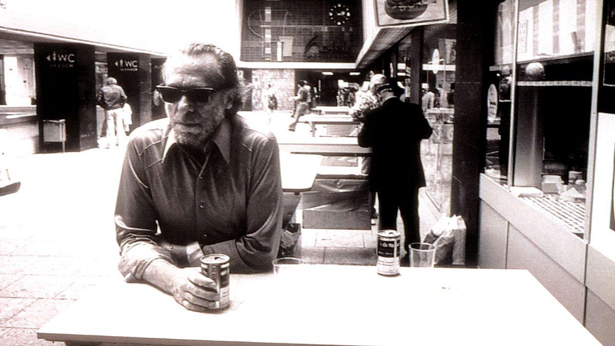 Charles Bukowski am Tresen mit einer Dose in der Hand.