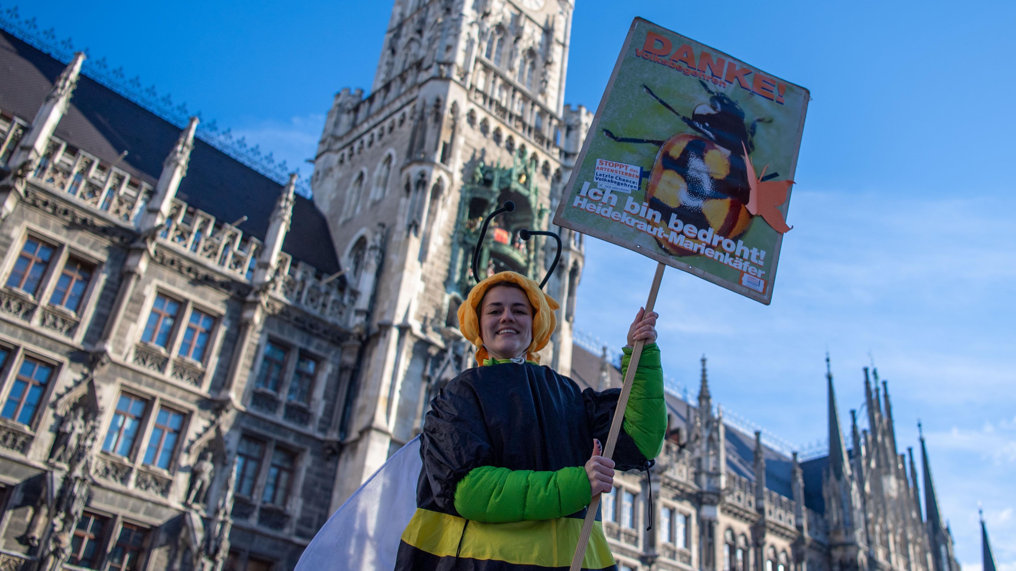 Aktivistin vom Bund Naturschutz steht in einem Bienenkostüm auf den Münchner Marienplatz und hält ein Plakat zum Volksbegehren hoch