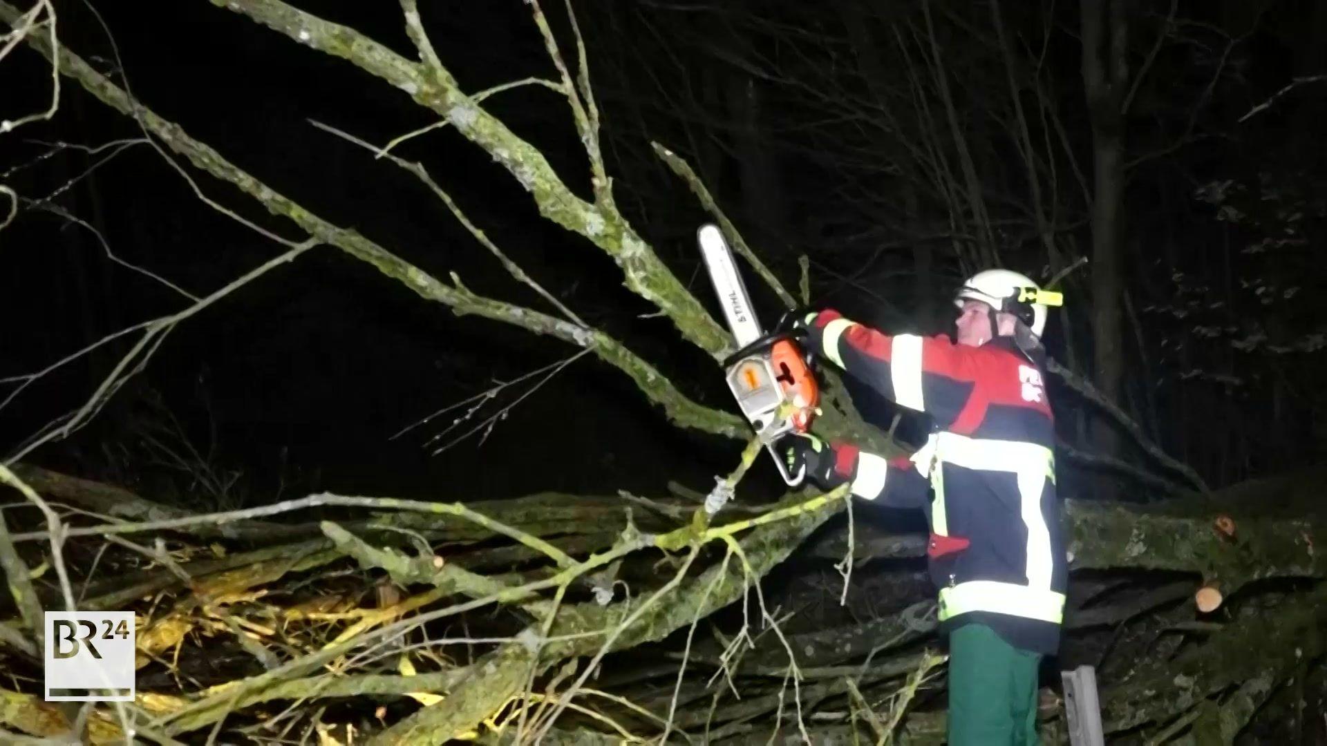 Ein Feuerwehrmann bearbeitet einen umgestürzten Baum mit der Motorsäge.