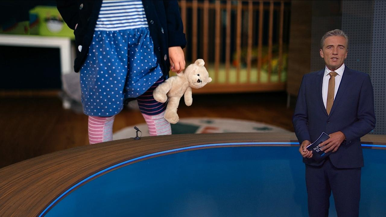 Moderator mit einem Bild, das ein Mädchen mit einem Teddybären zeigt
